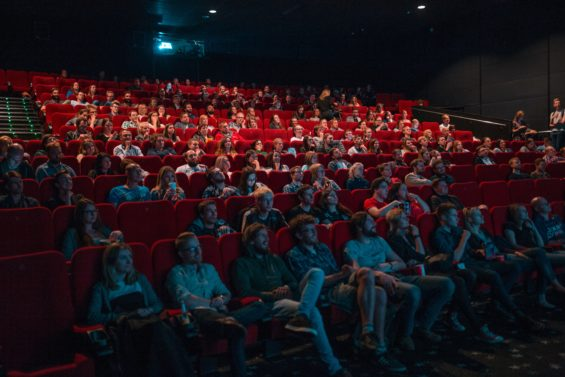 people in a movie theater- watch a movie to not forget a language